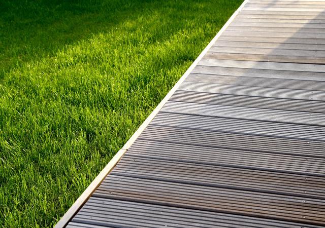 Unbehandeltes Holz kontrastiert schön mit dem Grün des Rasens.