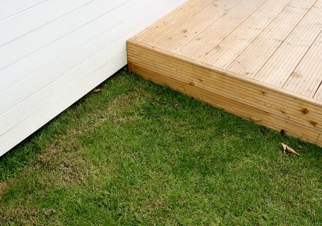 Nah am Haus verbindet ein Holzdeck die Architektur des Hauses mit der Gestaltung des Außenraums.