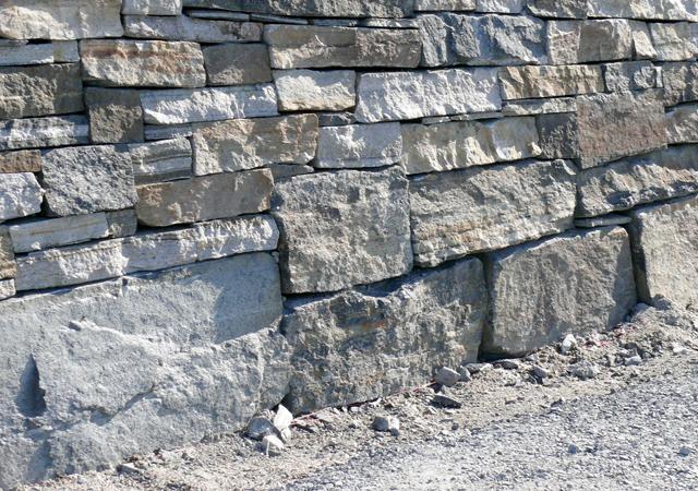 Natursteinmauerwerk mit großen Steinen an der Basis
